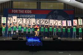 People holding signs with the amount raised at the IU Dance Marathon