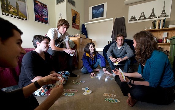 Students play a card game in dorm room