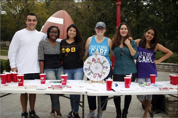 Students at culture of care spin wheel stall