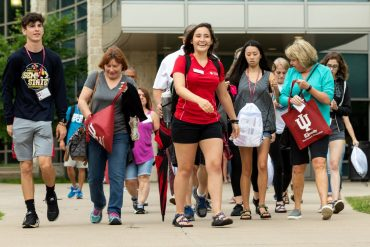 Students and parents walking on campus with OTEAM leader