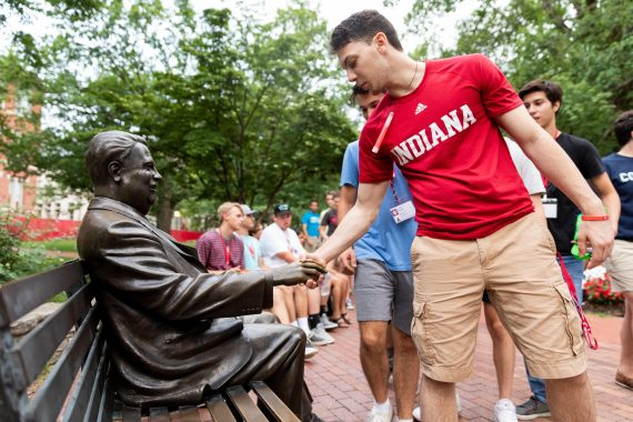 College student shaking hands with Herman B. Wells statue