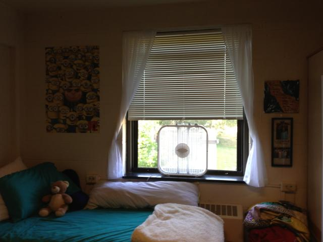 A bed, window and fan in a dorm room