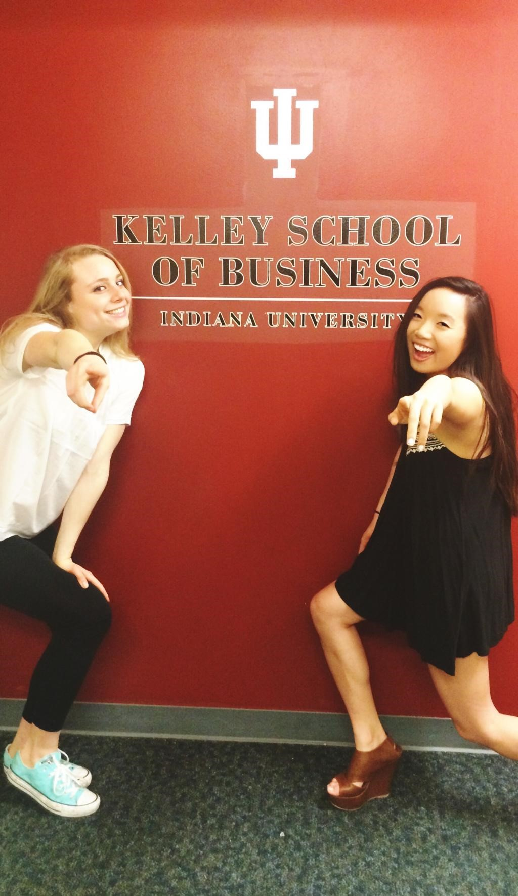 Girls posing infront of Kelly School of Business sign