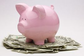 Piggybank on top of a pile of money