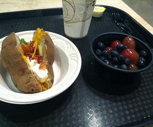 A baked potato and a cup of fruit