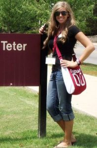 A girl standing next to Teter sign