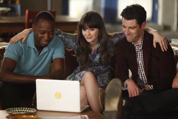 Friends sitting around a laptop